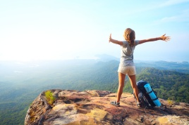 Young happy woman with backpack standing on a rock with raised hands and looking to a valley below