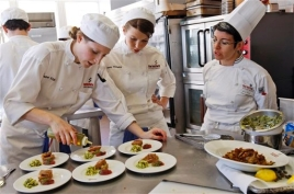 Chef instructor Erica Wides, right, watches student Jennifer Etzkin drizzle olive oil on a tuna appetizer she made as Abby Olitzky, watches during a class at the Institute of Culinary Education in New York, Wednesday, Feb. 25, 2009.  (AP Photo/Kathy Willens)
